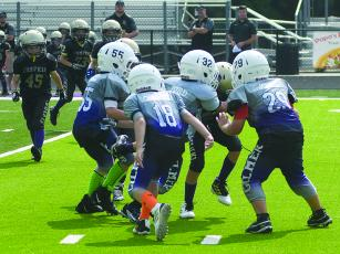 Gilmer's 8U defenders rally to make a tackle and will travel to White County Saturday to play the Warriors.