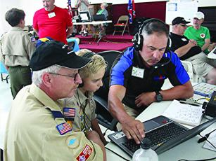 Ron Cheslock, of the Ellijay Amateur Radio Society (EARS), right, shows Tommy Parker, left, and son, Tommy Parker Jr., both of Cub Scout Pack 404, some of the equipment used by local ham radio operators during an EARS Field Day earlier this year.