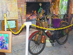 The uniquely outfitted bicycle once ridden by the late RT Henson will be on display at the Gilmer Chamber's Downtown Ellijay Welcome Center from Oct. 11-20. The lacquered bike is seen above next to a painting of Henson by artist Daniel Norris during a 2009 public tour of the artist and inventor's equally unique Ellijay home.