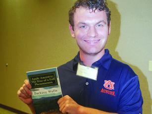 Zachary Walls holds a copy of his first book, Apple Ancestry: The Rise of a Fall Phenomenon.