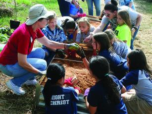 Lisa Harrison, of the Garden Club of Ellijay, left, shows a class at North Georgia Christian Academy how to prepare soil for a raised bed vegetable garden.
