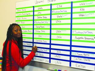 Latrice Richardson, coordinator of the federally-funded Upward Bound program at Gilmer High School, keeps track of students' college campus visits on one of two boards.