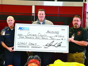 Gilmer County Fire Chief Daniel Kauffman, left, and EMA Director Keith Kucera, right, accept a safety grant check from ACCG representative Joe Dan Thompson.