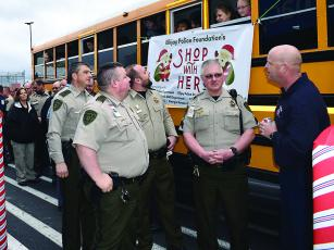 From left, Maj. Adam Smith, Capt. Brian Crump, Lt. Josh Chancey and Sgt. Greg Dotson, of the Gilmer Sheriff's Office, and Brian Scudder, of Gilmer Fire and Rescue, wait in front of the East Ellijay Walmart to be paired with children participating in the Shop With a Hero program.
