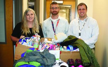 Gilmer High School Assistant Principals Todd Gearhart, center, and Matt Johnson, right, accept Bring a Bundle Clothing Drive donations from Times-Courier typesetter April Teague, left.