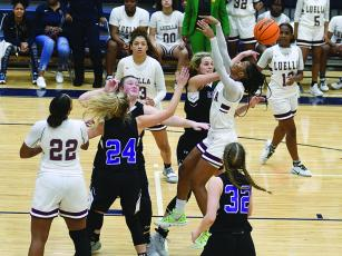 Gilmer's Elly Callihan tallies one of her four blocks as she rejects Luella's Keely Brown last Wednesday as teammates Jalynn Ledford and Emma Callihan (24) help defend the post.