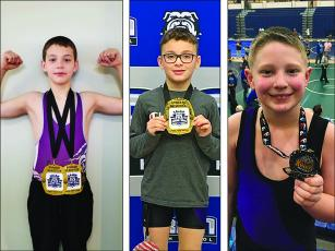 From left, are Gilmer youth wrestlers Isaiah Goodwin, Keigan Brookshire and Parker Settel. Goodwin and Brookshire both finished first in their weight class at last weekend's tournament in Trion. Goodwin and Settel also won a champion's belt for points accumulated based on their finishes at six tournaments during the USA Wrestling season.