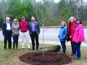 Garden Club of Ellijay members Scarlet Howard, Bonnie Waldron and Joanne Waddey, fifth from left to right, and Heath Lee, Gilmer County Library manager, fourth from left,  are joined by Jack Nunn, Lou Anne Nunn and George Bunch III, all family of founding garden club member Annetta Bunch, for a special Arbor Day tree planting in front of the library.
