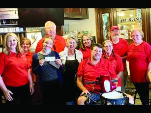 Friends of the Gilmer Animal Shelter (FOGAS) members Rebecca Harrell, Meg Eanes, Tim Vellenoweth, Marla Swanberg, Ernie Taylor, Sylvia Harris, Jack Peaden and Susan Lebert accept a $500 donation from Sammie Jo Hawkins and Terrie Leyden, of Cornerstone Cafe, third and fourth from left.