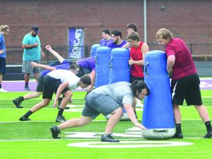 Gilmer High offensive linemen work on their blocking technique during a conditioning session last Wednesday.