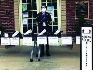 Gilmer County Library Sidewalk service is how the Gilmer County Library is safely checking out books and other material to customers. Above, staff member Cortny Crawford puts reserved material on the sidewalk service table in front of the local library.