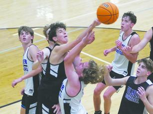 White's Cooper Bozzo draws a foul against Black's Britt Taylor during last Tuesday's basketball scrimmage.