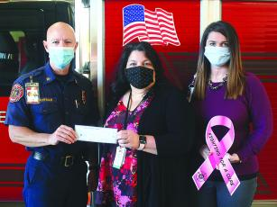 Gilmer County Fire Chief Daniel Kauffman presents a check from the public safety agency's recent Fighting for a Cure fundraiser to Piedmont Mountainside Radiology Clinical Manager Jennifer Nestor, center, and Piedmont Mountainside Director of Imaging Services Brandi Baldwin, right. The funds will be used to provide reduced-cost mammograms for 13 local women.