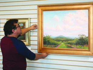 Jesus Morales, of the Gilmer Arts Gallery, straightens a painting by Atlanta artist Jill McGannon, whose work comprises one of three exhibits now on display at the downtown Ellijay gallery.