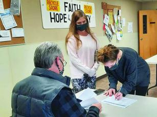 Kent Sanford, of the Faith, Hope and Charity Scholarship Committee, helps two students during the nonprofit's recent award process for the spring college semester.