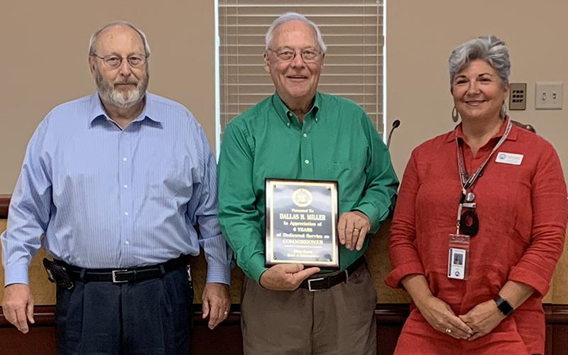 Gilmer County Post 1 Commissioner Dallas Miller (center) receives a plaque for his service at his last meeting on Sept. 12, from Chairman Charlie Paris and Post 2 Commissioner Karleen Ferguson. Miller's resignation from the board was effective Sept. 13.