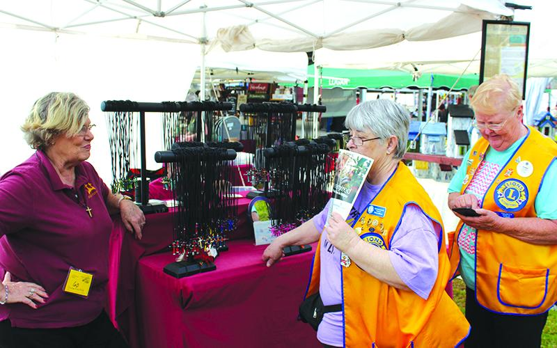 Proprietor Anne Bond, of Newnan, talks with regional Lions Club members Donna Calhoun (Chickamauga), left, and Jan Morris (Trion), about her Crosses from Nails booth just before the Apple Festival gates opened Saturday.