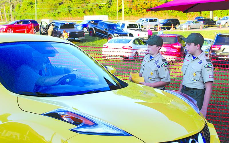 Bryson Petkus, left, and Clay McConnell, both age 11, take up parking donations at the Apple Festival fairgrounds Saturday morning that will help fund Troop 402 programs throughout the year.