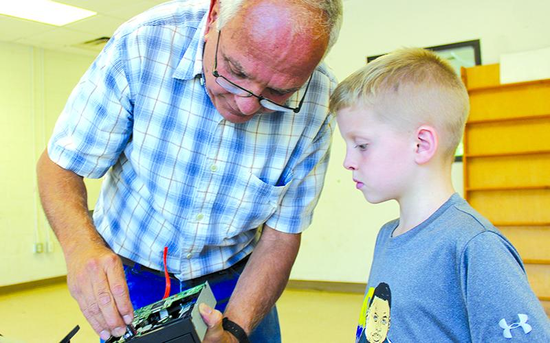 "Jaxon Sevcech, 7, watches as volunteer Mickey Moskovitz explains how a DVD disc drawer works. The ""Deconstruction Zone"" at the Three Rivers Boys and Girls Club is a popular once-a-week class."