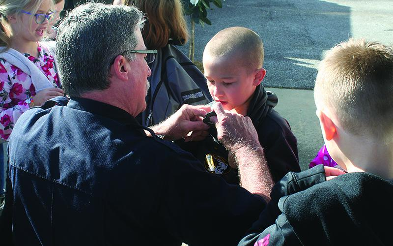 Firefighter Jeff Statham pins a junior fire chief badge onto Nolan Tatum, one of the local second graders who completed the Ellijay Fire Department's safety and prevention course this year.