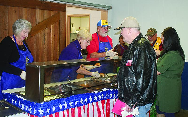 Ellijay Lions Bonnie Dixon, Susan Harden and Charlie Dixon serve barbecue and fixings to appreciative attendees.