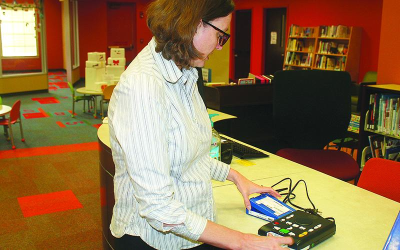 Jessica Tibbetts, adult services coordinator at the Gilmer County Library, demonstrates a GLASS talking book reader that can be used by persons with eyesight challenges.