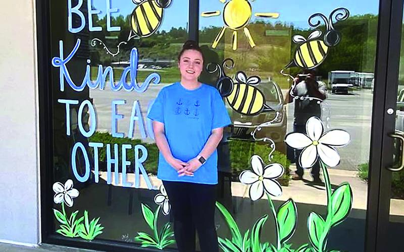 Abby Dotson is pictured in front of a mural she painted in the window of Double L Restaurant.