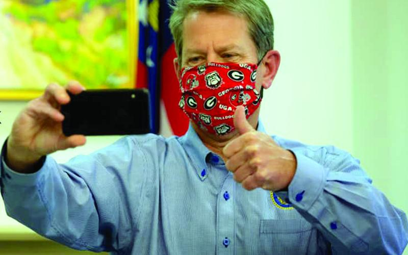 "Gov. Brian Kemp posted this photo on social media with the caption, ""Wear your mask, Georgia — and Go Dawgs!"" Kemp is traveling the state this week to encourage citizens to wear a mask in public to help stop the spread of the coronavirus."