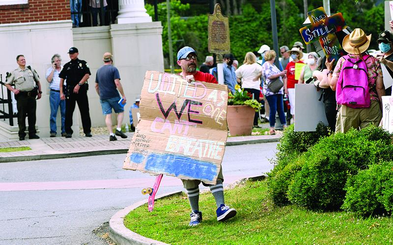 A crowd of people hold up signs during a rally on the square in downtown Ellijay on June 4. Organizers said  the wanted to give people a place to voice their frustrations and concerns over racism.