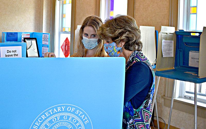 Kathy Tankersley assists Leah Davis during early voting at the Gilmer County Courthouse for the Aug. 11, primary runoff.
