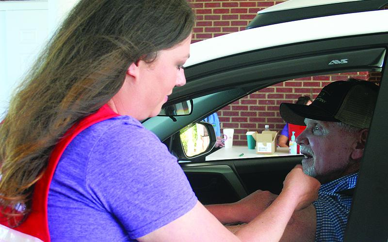 Gilmer Health Department nurse Jennifer Vick vaccinates a patient during one of the health department's past drive-thru flu shot clinics.