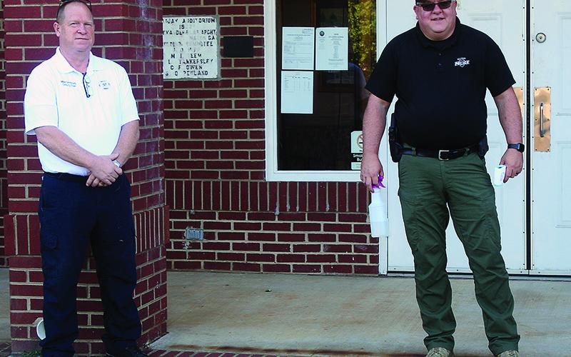 Before you enter ... Ellijay Deputy Fire Chief Mike Dempsey, left, and Ellijay Police Capt. Ray Grace are pictured outside City Hall checking temperatures and dispensing hand sanitizer for attendees at this month's Ellijay City Council meeting.