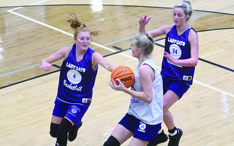Gilmer Lady Cats Hope Colwell (4) and Emma Callihan (24) try to slow Lark Reece in transition during the Purple and White game. The trio will all receive significant varsity minutes this season.