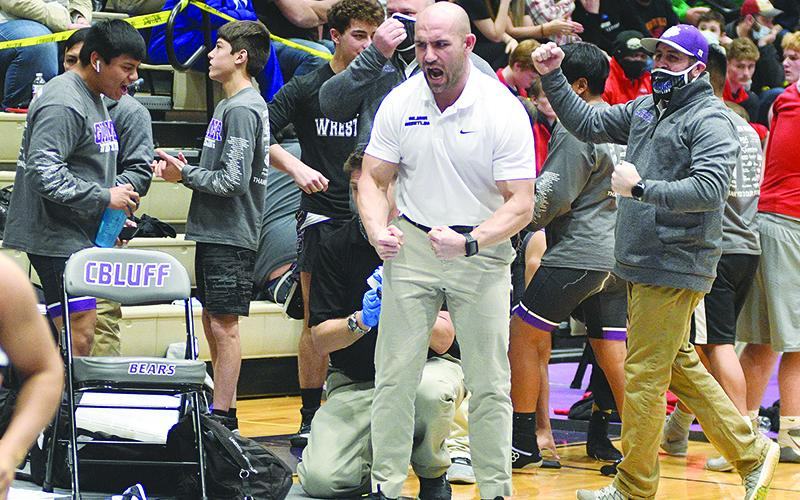 From left, Gilmer High head coach Josh Ghobadpoor and assistant Brent Berry react to a one of the Bobcats' victories during the Class 3A state duals tournament.